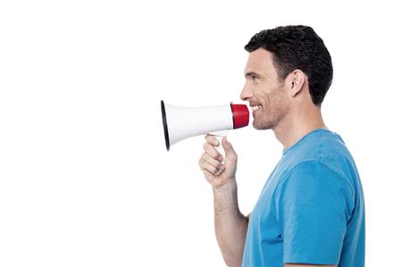 loudhailer: Sideways of casual man proclaiming into loudhailer
