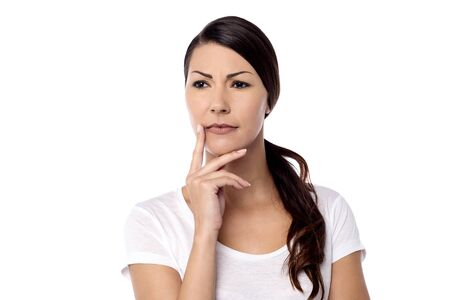 skeptic: Pensive woman touching her face over white Stock Photo
