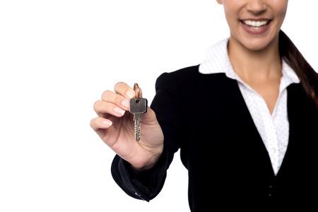 agente comercial: Imagen cosechada de la agente de bienes ra�ces que ofrece llave de la casa