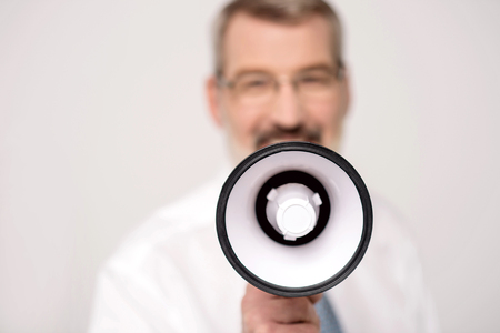 making an announcement: Happy man making announcement over a loudhailer