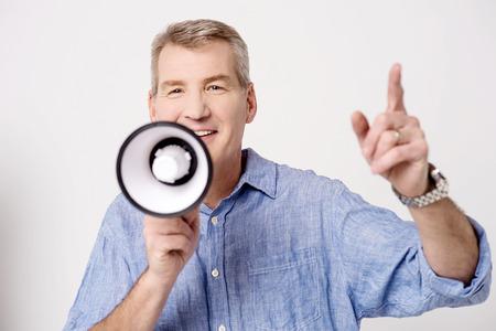 mega phone: Mature man with mega phone and pointing up