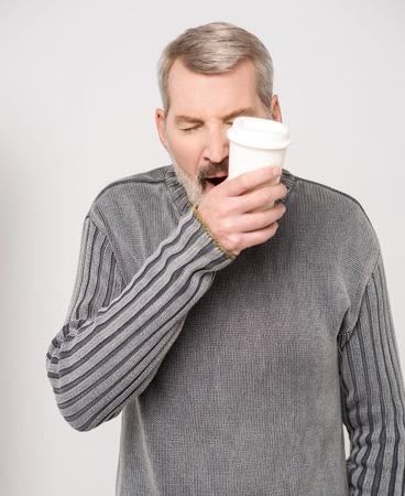 sleepy man: Sleepy man is yawning with a cup of coffee Stock Photo