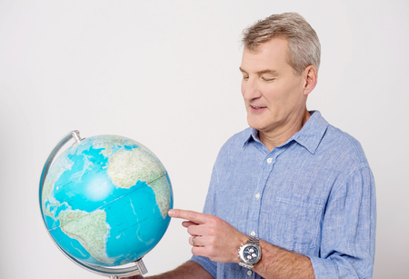 other world: Senior man pointing his finger on globe