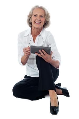 seated: Seated elderly woman operating digital tablet