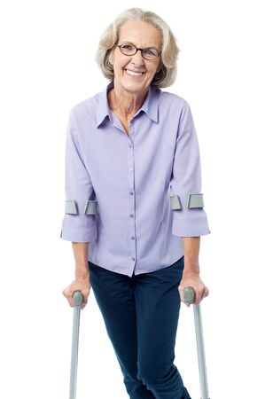 crutches: Senior woman walking with help of crutches Stock Photo