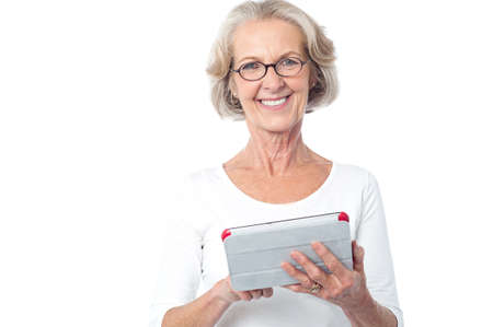 happy old people: Smiling mature woman holding tablet in her hands Stock Photo
