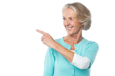 space   area: Mature woman pointing the copy space area