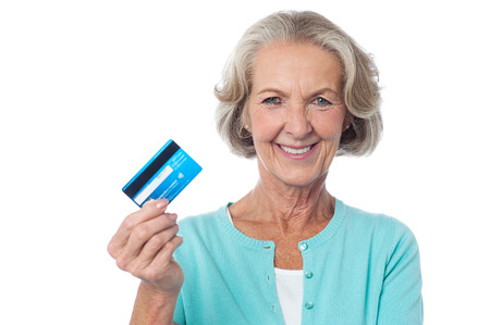 Mature woman showing her debit card to camera