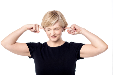 plugging: Stressed woman plugging ears with fingers Stock Photo