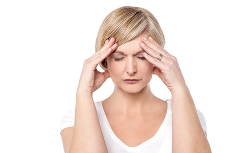 片頭痛、彼女の頭を保持している心配している女性。 写真素材