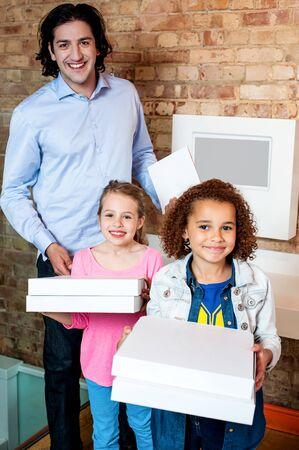 ni�as peque�as: Ni�as peque�os felices que presentan con cajas de pizza
