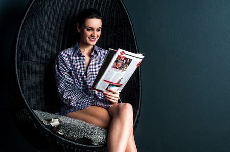 Happy woman sitting on bubble chair and reading magazine