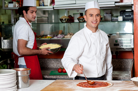 pizza base: Male chef preparing the pizza base with sauce