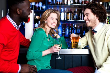 Group of three friends in a bar having drinks photo