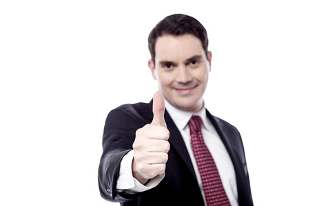 posing  agree: Happy businessman showing thumbs up gesture