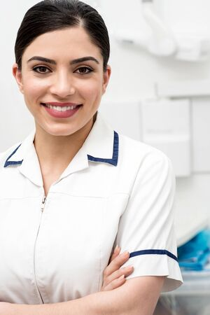Confident female dental assistant posing in clinic photo