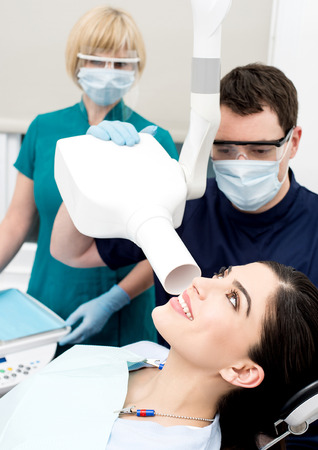 x ray machine: Male dentist takes jaw x-ray of female patient