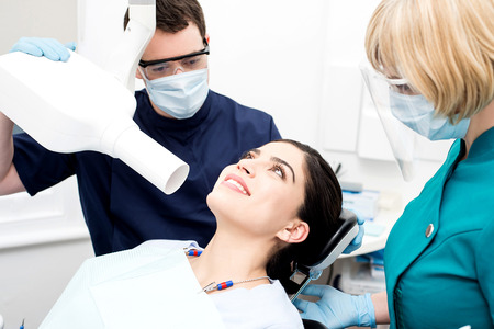 x ray machine: Male dentist takes an x-ray of an woman teeth
