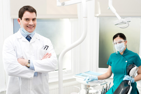 Confident dentist his female assistant posing behind photo