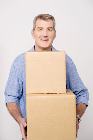 man carrying: Middle aged man carrying stack of carton boxes