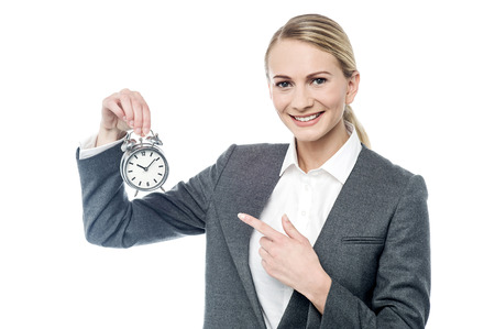 tardy: Female executive pointing her finger at alarm clock