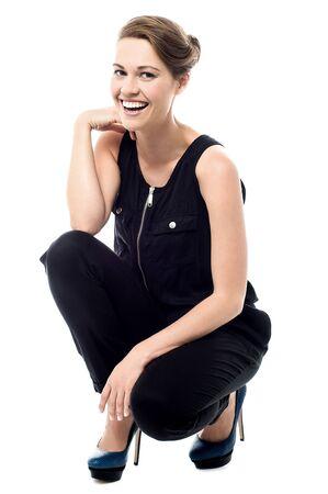 cuclillas: Mujer feliz que presenta en una posici�n en cuclillas