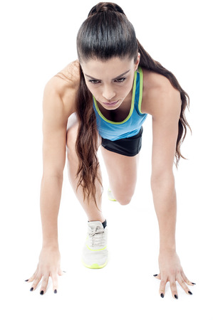 crouched: Woman athlete crouched down in starting position