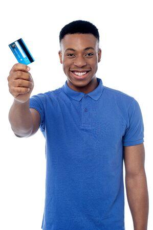 debit card: Young man showing his debit card to camera Stock Photo