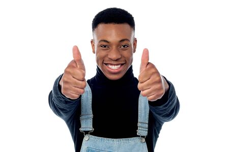 posing  agree: Young man making a double thumbs up gesture Stock Photo