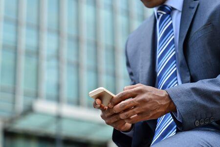 携帯電話を介してメッセージを送信する実業家のトリミングの画像 写真素材