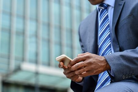 african american: Cropped image of businessman sending messages via mobile