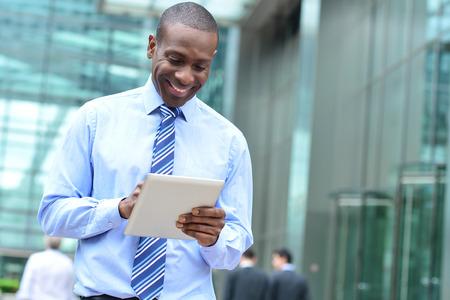 digital tablet: Smiling businessman using his new digital tablet Stock Photo