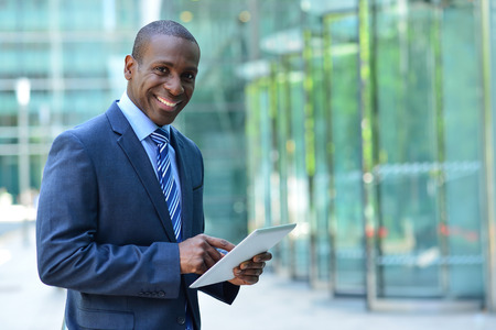 Confident male entrepreneur posing with digital tablet