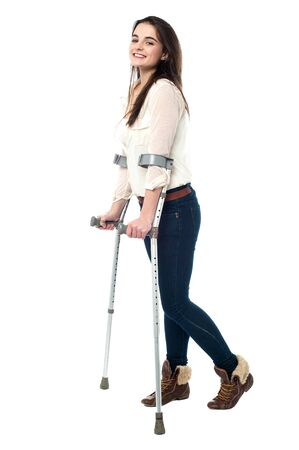 crutches: Trendy young girl walking with crutches
