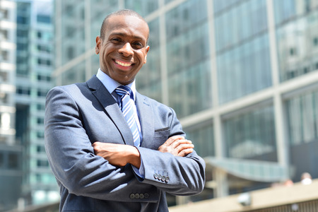 businessman smiling: Successful businessman posing with crossed arms
