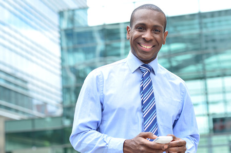 building business: Happy male executive posing with his mobile phone