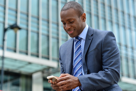 Smiling Geschäftsmann sucht auf seinem Handy