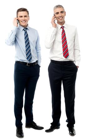 gente comunicandose: Los j�venes empresarios que se comunican a trav�s del tel�fono m�vil Foto de archivo