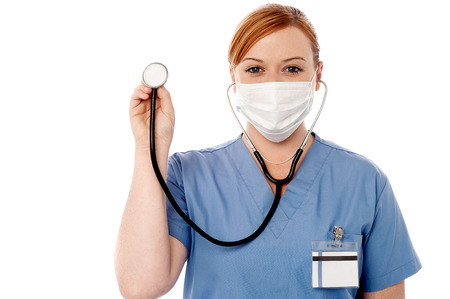 doctor with mask: Female doctor holding up a stethoscope Stock Photo