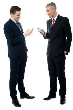 full length: Volledige lengte van mensen uit het bedrijfsleven bespreken met een mobiele telefoon