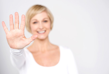 middle aged women: Smiling woman making high five with her hand