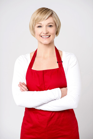 Smiling chef woman posing with arms crossed Stock Photo