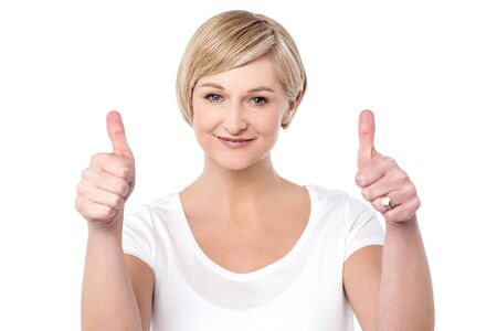 posing  agree: Successful woman making thumbs up gesture