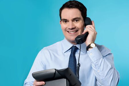 answering: Happy male executive answering a phone call