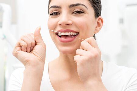 diente: Mujer que usa la seda dental para limpiar sus dientes