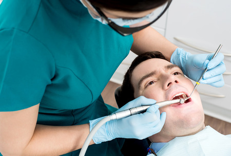 Male with open mouth during oral checkup at dentist Stock Photo
