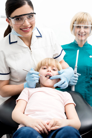 Dentist and assistant examining a little girl patient photo