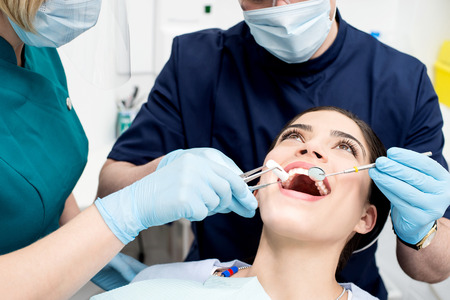 Dentist treating patient teeth with assistant photo