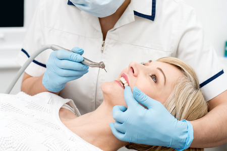 Female patient getting treatment from dentist Stock Photo - 39290796
