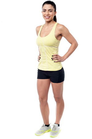 fitness trainer: Full length of athletic woman with hands on waist